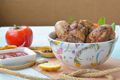 Dish full of grilled chicken wings and legs near spices, sauce. On table Stock Photography