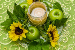 Dish with green apples, flowers and candle Stock Photo