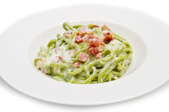 Dish of green spaghetti with bacon and cream. A dish of green spaghetti with bacon and cream Stock Photo