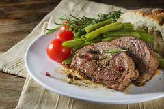 Dish of grilled lamb steak with green beans, tomatoes and bread Stock Photography