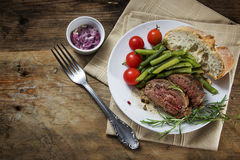 Dish of grilled rosemary lamb steak with green beans, tomatoes, Royalty Free Stock Photography