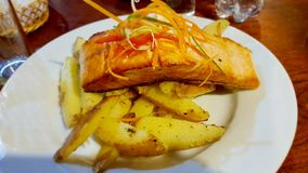 A dish of grilled salmon with baked potatoes. San Pedro de Atacama, Cile stock images