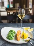 Dish with grilled salmon with lemon slices and white wine on table. Close up view Stock Image