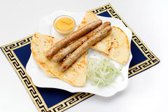 Dish with grilled sausages, pita bread, mustard Stock Photography