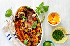 Dish healthy beef meat baked vegetables white rustic wooden tabl. Dish of beef meat baked with vegetables potatoes, carrots, eggplant, zucchini and tomato in Stock Photos