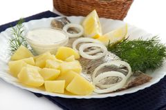 Dish with herring and potatoes. Dish with a herring and potatoes on a napkin, closeup, isolated on white Royalty Free Stock Image