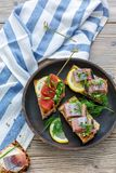 Toasted bread with herring, caviar and greens. Royalty Free Stock Photography