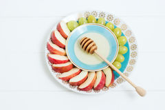 Dish with honey, fruit on white background. Jewish NY, Rosh Hashanah. Selective focus, small depth of field, lensbaby. Dish with honey, fruit and a spoon for Stock Images