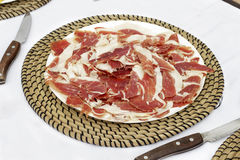 Dish of iberian ham slices over white tablecloth Royalty Free Stock Image