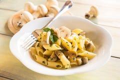 Champignon Mushroom Italian Pasta Dish. Dish of italian penne rigate pasta with champignon mushrooms and parsley Stock Photos