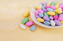 Dish of Jordan Almonds on Yellow Tablecloth Royalty Free Stock Images