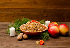 Dish with kutia - traditional Christmas treat of the Slavs on Christmas Eve. Fur-tree branch, apple, candle on a wooden background Stock Photos