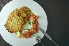 Dish Marinated salmon with dill and potato pancakes on a wooden table. fresh salted trout. dish on a plate. Russian food. Dish Marinated salmon with dill and royalty free stock images