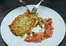 Dish Marinated salmon with dill and potato pancakes on a wooden table. fresh salted trout. dish on a plate. Russian food. Dish Marinated salmon with dill and stock photos