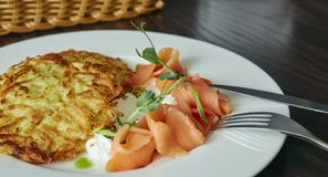 Dish Marinated salmon with dill and potato pancakes on a wooden table. fresh salted trout. dish on a plate. Russian food. Dish Marinated salmon with dill and stock image