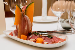 Dish with meat and slices of melon Stock Photo