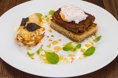 Dish with meat steak on toast, potato chips  melted cheese and poached egg  Dutch sauce. Wooden background. Top view Stock Photos