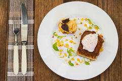 Dish with meat steak on toast, potato chips  melted cheese and poached egg  Dutch sauce. Wooden background. Top view Royalty Free Stock Images