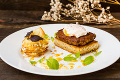 Dish with meat steak on toast, potato chips  melted cheese and poached egg  Dutch sauce. Wooden background. Top view Royalty Free Stock Photo
