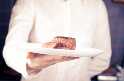 Dish of medallions in one hand. Chef keeps a dish of medallions in one hand Royalty Free Stock Images