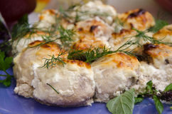 Champignons baked with sour cream and greens. Dish of mushrooms marinated in sour cream, decorated with greens, an example of serving Stock Photos