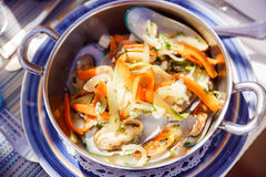 Dish with mussels and vegetables in a metal pan on the served ta Stock Photo