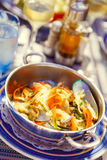 Dish with mussels and vegetables in a metal pan on the served ta Stock Images