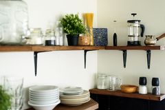 Dish on open shelves in kitchen. Dish and decorations on open wooden shelves in white kitchen stock photo