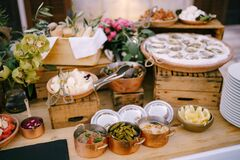 A dish with oysters, pickles and casseroles with treats for guests on a blurred background on a wooden table.