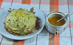 Dish with the pancakes and bowl of honey. On the tablecloth closeup Stock Photography