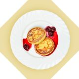 Dish of pancakes with cherry sause on white plate. Royalty Free Stock Photo
