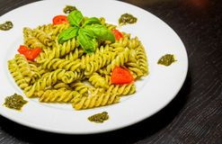 Dish of pasta with pesto genovese sauce and vegetables, tomato and basil Stock Photography