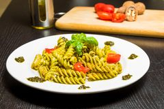 Dish of pasta with pesto genovese sauce and vegetables, tomato and basil on black wood table Stock Images