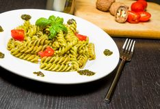 Dish of pasta with pesto genovese sauce and vegetables, tomato and basil on black wood table near fork Royalty Free Stock Photography