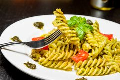 Dish of pasta with pesto genovese sauce and vegetables, tomato and basil, detail of fork with fusilli on top Stock Images