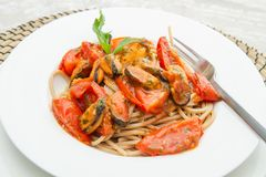 Dish with Pasta spaghetti , mussel and tomatoes. White dish with Pasta spaghetti , mussel and tomatoes Royalty Free Stock Photo