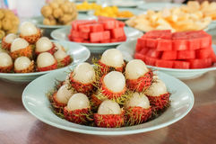 A dish of peeled rambutan. With various fruit in background Royalty Free Stock Image