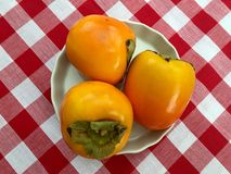 Dish of permission. A small white dish containing three persimmon fruit displayed on a red and white gingham tablecloth Royalty Free Stock Image