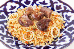 Dish with pilaf Uzbek dishes, garlic, onions, carrots, tomatoes, beef, meat, large, isolated on a white background. For the menu Royalty Free Stock Photos