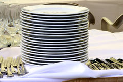 Dish pile. Pile od clean dishes together with forks and knifes ready to start a party Royalty Free Stock Images