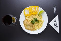 Dish in plate and glass of red wine over dinner top view. pasta and chop with slices of yellow pepper on serving table. Dish in plate and glass of red wine over Royalty Free Stock Photos