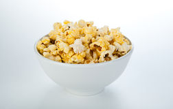 Dish with popcorn on white Royalty Free Stock Photo