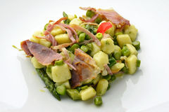 Dish of Potato Dumplings with Asparagus and Crispy Ham. On white plate Stock Images
