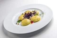 Dish of potato ravioli with crustacean ragout and berries. On white background stock photography