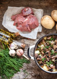 Dish of potatoes with mushrooms on a wooden background and raw i Royalty Free Stock Photo