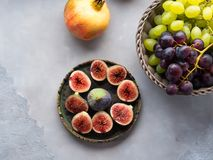 Dish of purple figs, grapes and pomegranate Stock Images