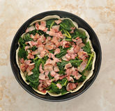 Dish quiche before baking in the oven. bacon, spinach, thin crus. T. top view Stock Photography