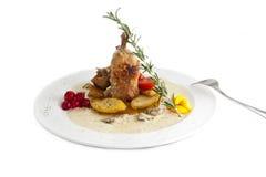 Dish from a rabbit, a potato, tomatoes stock photo