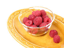 Dish of Raspberries. A dish of raspberries rests on a yellow plate royalty free stock photos