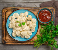 Dish with ravioli and red sauce on a wooden board. Top view Stock Photos